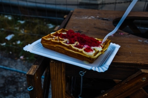 Waffle drenched in raspberries & vanilla sauce.